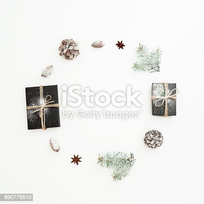 istock Christmas round frame made of stylish black gift box, fir branches and pine cones on white background. Flat lay. Top view 890779510