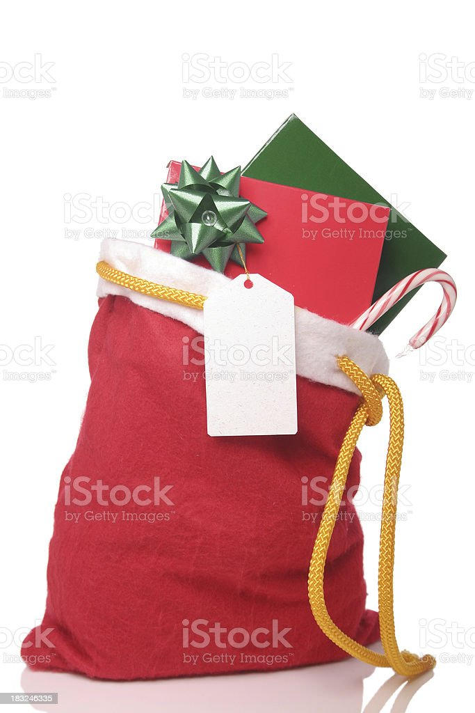 Christmas sack filled with candy cane card and gift with bow royalty-free stock photo