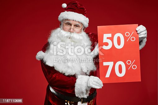 Portrait of Santa Claus in beautiful red costume showing sign of big sale and looking at camera