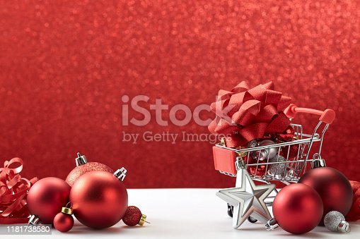 Conceptual photo of Supermarket trolley filled with Christmas sales decorations on a background of holiday red lights. Preparing for the New Year and Christmas. Buying gifts.
