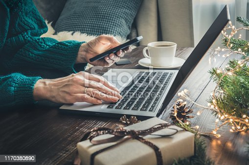 Christmas sales. Woman shopping with smartphone by laptop in home interior. Xmas concept. Planning holidays.
