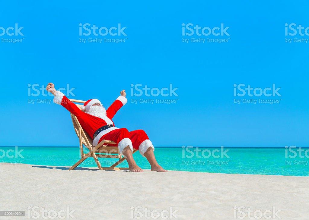 Christmas Santa Claus enjoy sun on deckchair at tropical beach stock photo