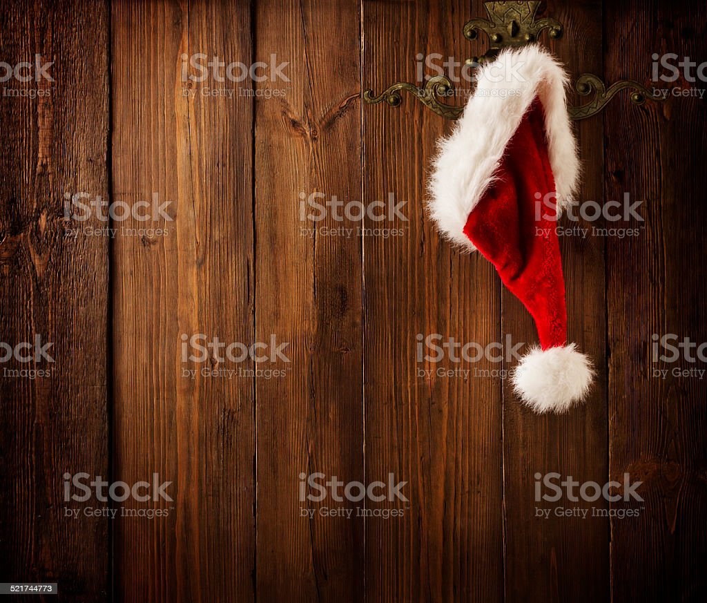 Christmas Santa Claus Hat Hanging On Wood Wall, Xmas Concept stock photo