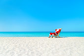 Christmas Santa Claus resting on deckchair at ocean sandy tropical beach - xmas travel vacation in hot countries concept