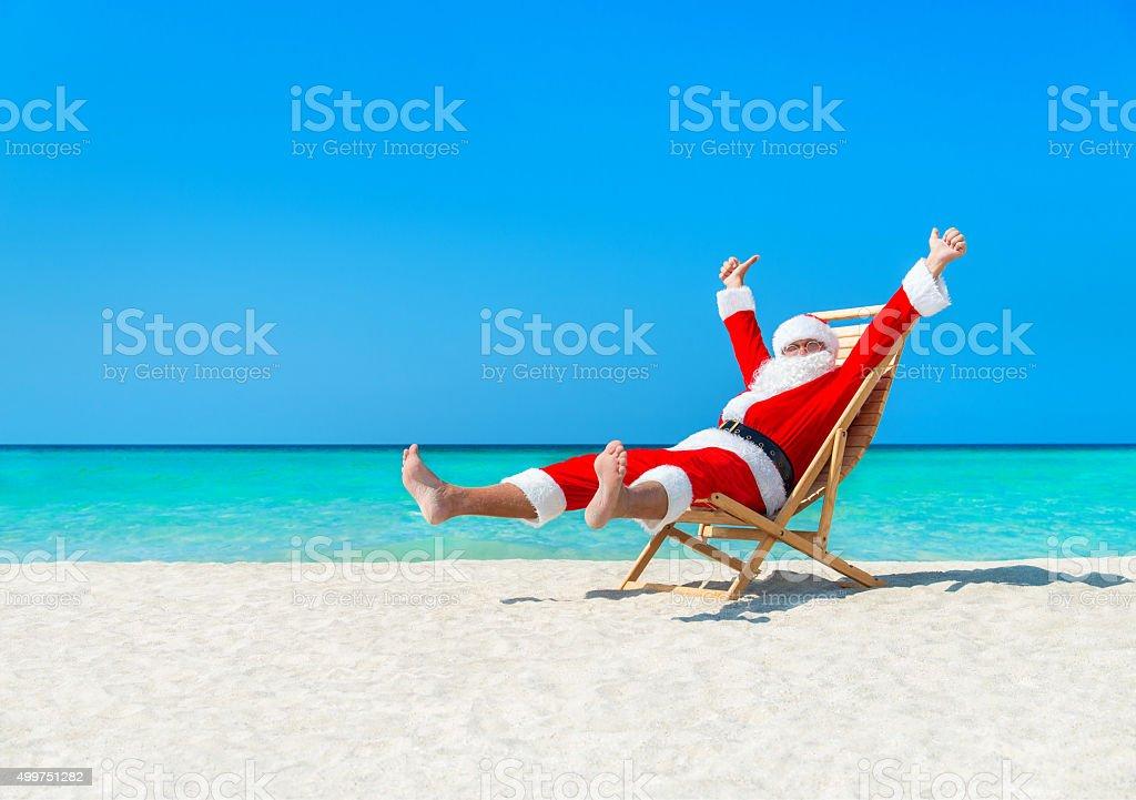 Christmas Santa Claus resting on deckchair at ocean sandy beach stock photo