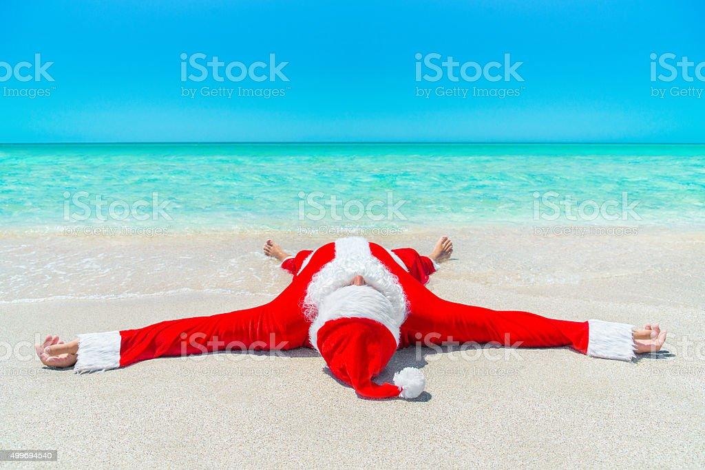 Christmas Santa Claus take pleasure sunbathing at tropical ocean stock photo
