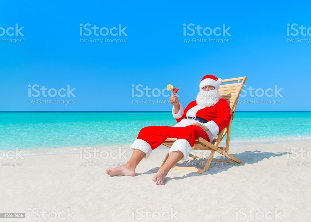 Christmas Santa Claus with cocktail on deck chair at beach stock photo