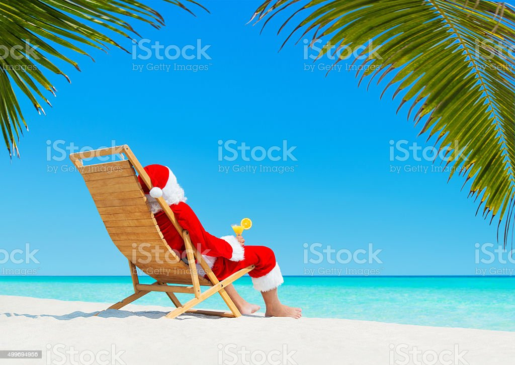 Christmas Santa Claus with cocktail on deckchair at tropical beach stock photo