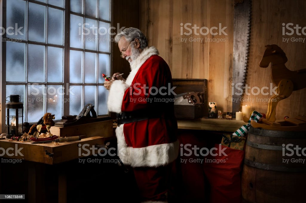 Christmas Santa Claus Working in His Toy Workshop, Copy Space stock photo