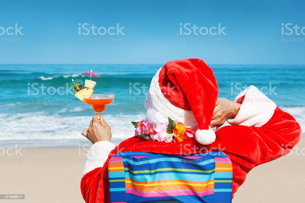 Christmas Santa Clause Vacationing on Tropical Beach with Drinks Hz royalty-free stock photo