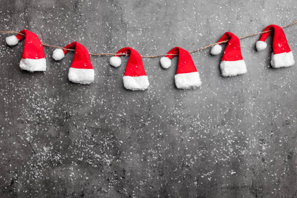 Christmas Santa hats on rustic background with copy space stock photo