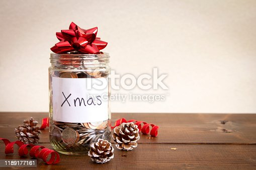 A jar of coins on a wooden table with Christmas decorations and a hand written sign, on a white background.