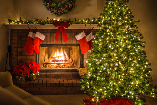 Christmas tree and decorations around the warmth of the blazing fire in the fireplace. Christmas tree, Christmas fireplace, stockings, lights, ornaments, poinsettias, bow.