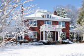 The photo depicts a winter Christmas Scene. A big brown and white house covered in snow with a U.S. flag on the front porch, is surrounded with several trees, and a garage on the right side. A balcony and beautiful plants near the entrance can also be seen. The sun is shining after a snowy day.