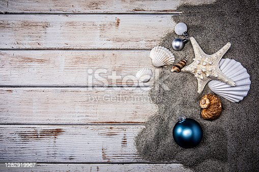 istock Christmas Seashells in the Sand on white wood background 1282919967