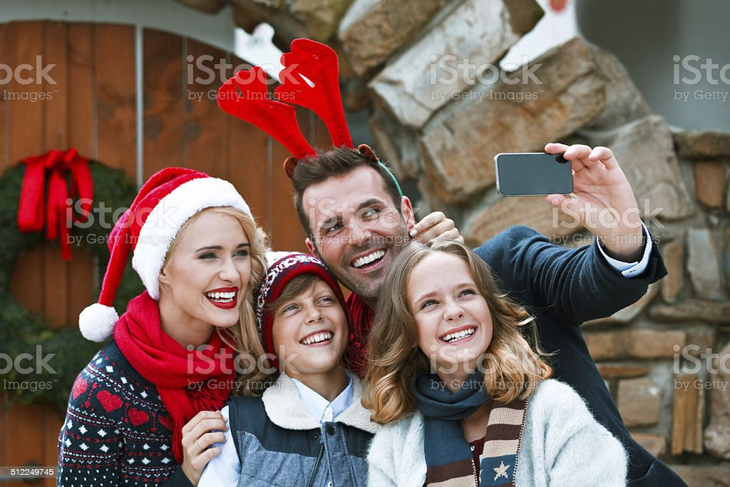 Christmas Selfie Happy family standing in front of entrance door and taking selfie. Mother wearing santa hat and father reindeer horns head band. 10-11 Years Stock Photo