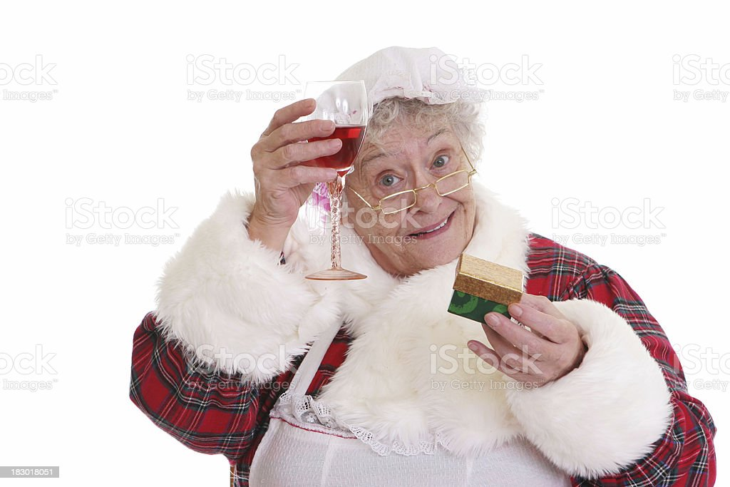 Christmas: Senior Mrs Claus holding gift and wine stock photo