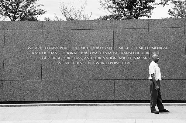 "Christmas sermon quote at the Martin Luther King Jr Memorial Washington DC, USA - June 13, 2012: An African-American man stands beside a quote at the Martin Luther King Jr Memorial in Washington DC. The quote is from a 1967 Christmas sermon in Atlanta, Georgia and reads: ""If we are to have peace on earth, our loyalties must become ecumenical rather than sectional. Our loyalties must transcend our race, our tribe, our class, and our nation; and this means we must develop a world perspective."" mlk stock pictures, royalty-free photos & images"