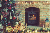 Toned photo of beautiful Christmas setting, decorated fireplace with woodburner, lit up Christmas tree with baubles and ornaments, lantern, stars and garlands, selective focus