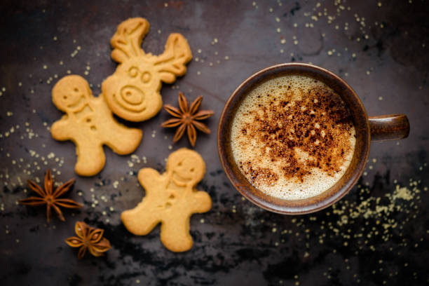 Christmas setting with festive cookies and coffee Christmas concept - festive gingerbread man and deer shaped cookies with a cup of cappuccino coffee against dark rustic background. Overhead view december stock pictures, royalty-free photos & images