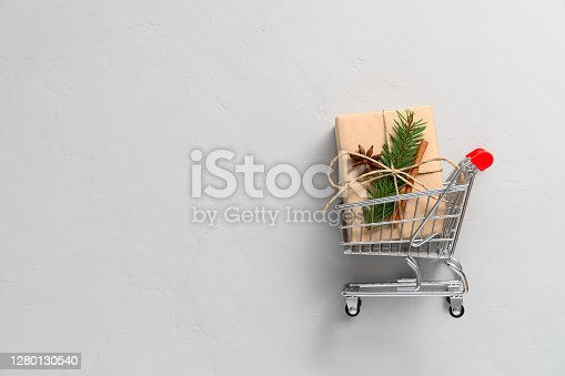 Christmas shopping concept. Top view of shopping cart and gift box on light gray background. Copy space, flat lay. Winter holidays sales.