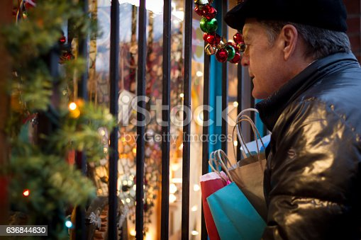 621898406istockphoto Christmas Shopping: Man with Shopping Bags Peers into Shop Window 636844630
