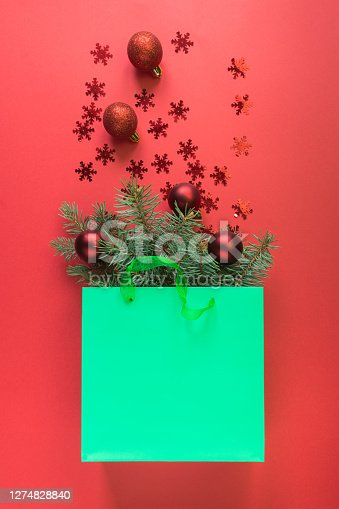 Christmas shopping green paper bag with red baubles and shiny snowflakes on red background. Xmas concept. View from above, flat lay.