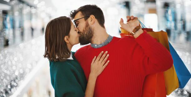 christmas shopping. - brunette woman eyeglasses kiss man foto e immagini stock