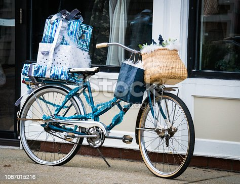 An old bicycle is decorated for Christmas and loaded with brightly  wrapped presents.