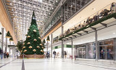 Shopping mall with Christmas tree and decoration with lots of shops and stores.
