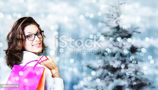 istock christmas shopping, smiling woman with bags on blurred bright li 860599316