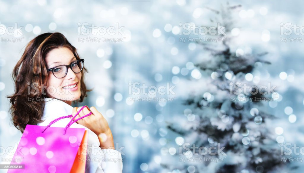 christmas shopping, smiling woman with bags on blurred bright li stock photo