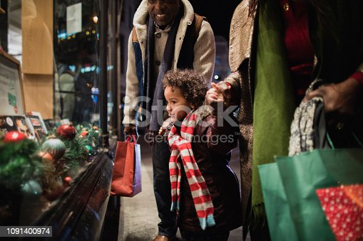 A side-view shot of two grandparents standing outside of a store window with their granddaughter in the city on a cold night, they are wearing warm clothing and holding hands.