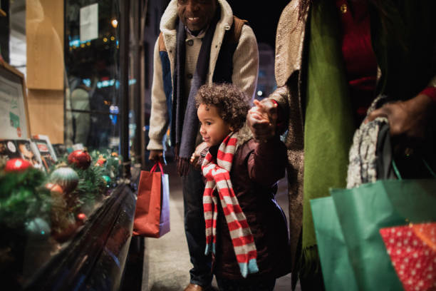Christmas Shopping with Grandparents A side-view shot of two grandparents standing outside of a store window with their granddaughter in the city on a cold night, they are wearing warm clothing and holding hands. buying stock pictures, royalty-free photos & images