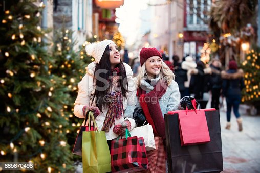 Two best friends shopping for Christmas in the old town Quebec city. They have fun playing tourists. They wear mittens and toques coats. Shopping in decorated and busy streets, browsing shop windows, choosing gifts, carrying lots of bags full of presents, having a coffee break or a meal after shopping, on the phone, checking technology.