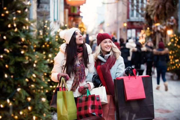weihnachts-shopping mit zwei jungen frauen - günstige weihnachtsgeschenke stock-fotos und bilder