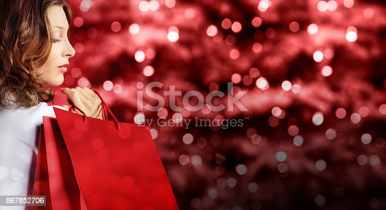 istock christmas shopping, woman with bag on red blurred bright lights 867852706