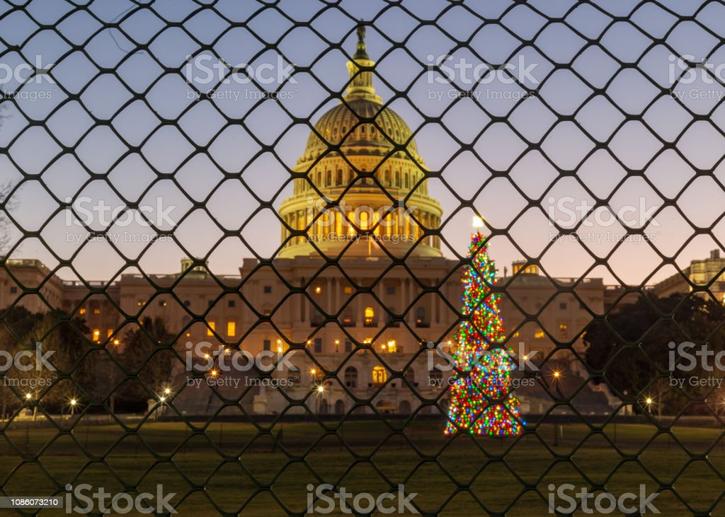 Christmas Shutdown Sunrise over the United States Capitol Building and the Capitol Christmas Tree, now fenced off from the public during the government shutdown. Boundary Stock Photo