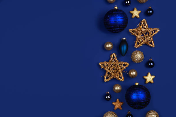 Christmas side border of dark blue and gold ornaments, top view on a blue background stock photo