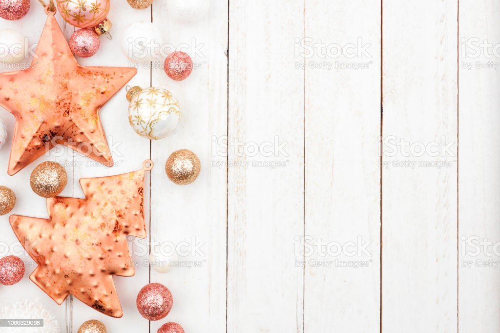 Christmas side border of rose gold, white and gold ornaments on a...