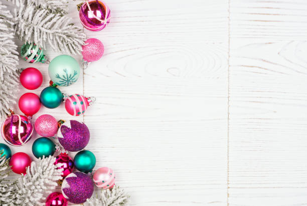 Christmas side border with pink, purple and teal ornaments and snowy branches, above view on a white wood background stock photo