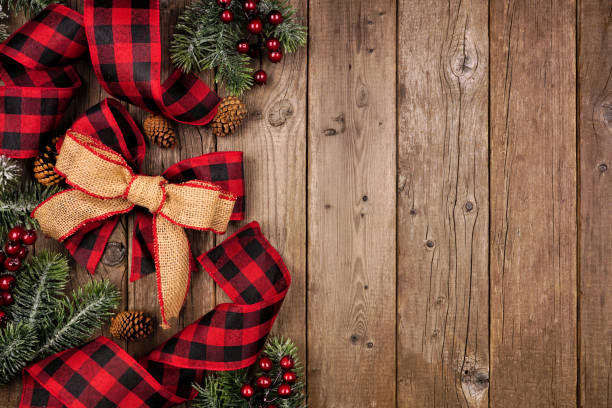 Christmas side border with red and black checked buffalo plaid ribbon, burlap and branches, overhead view on a wood background stock photo