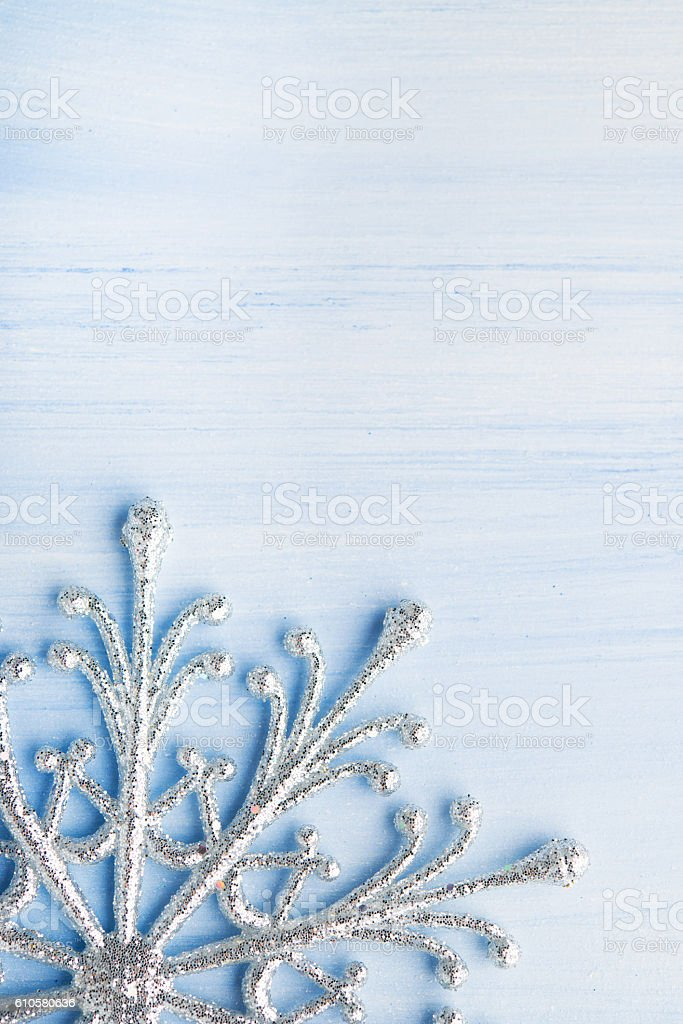 Christmas silver snowflake on light blue wood background stock photo