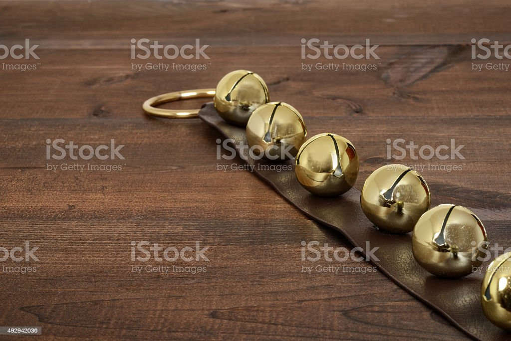 christmas sleigh bells on wood stock photo