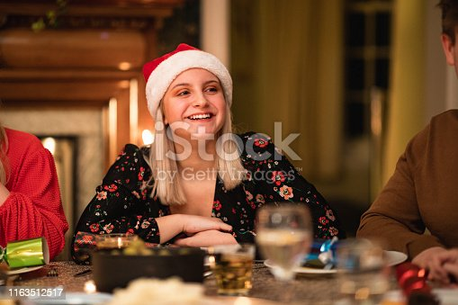 A beautiful young woman wearing a Santa hat can be seen sitting at the dinner table on Christmas Day, she is laughing and smiling.
