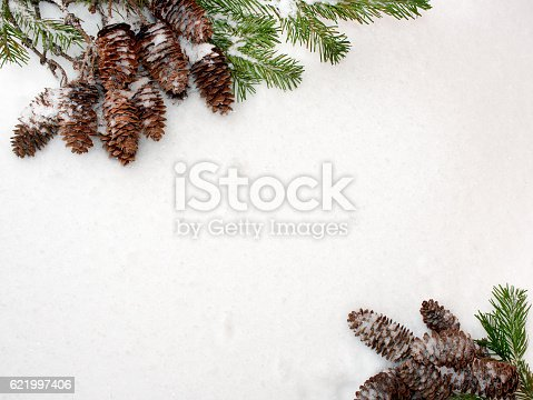 Christmas background. Green spruce branches and cones, are located diagonally opposite each other, on the white snow.