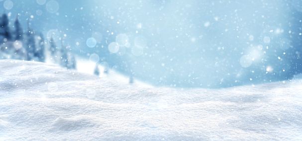 Winter and christmas snow background with snowdrifts and snow-covered blur forest.