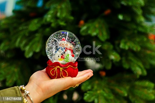 Christmas snowball toy in the hand of a young girl.