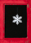 Christmas Snowflake Decoration in Red-Framed Window Close-Up