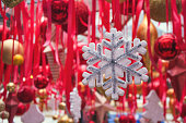 Christmas snowflakes in fair kiosk with red handcrafted xmas decorations. Close up.